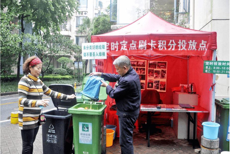 业主李莎莉与垃圾分类指导员一同将垃圾进行分类