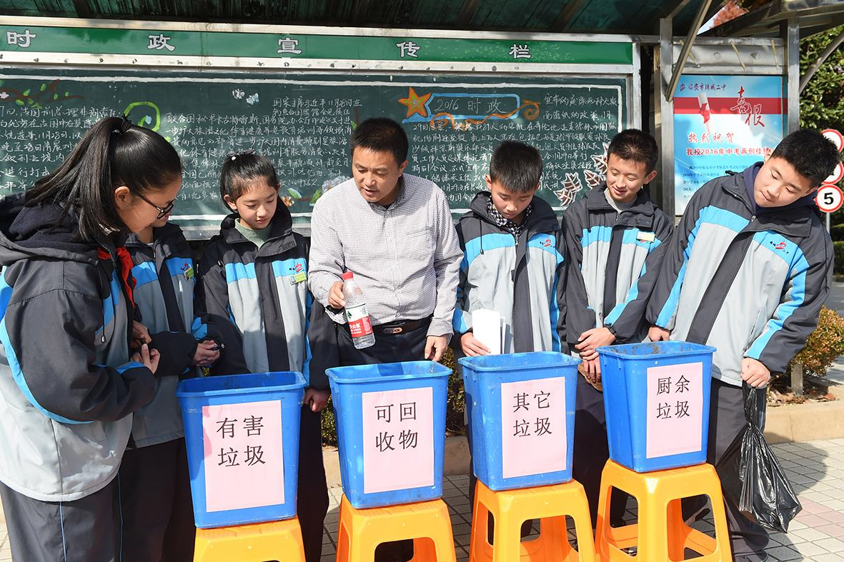 近日,在锦城二中的校园里,几名学生正在老师的监督下完成垃圾分类活动举办